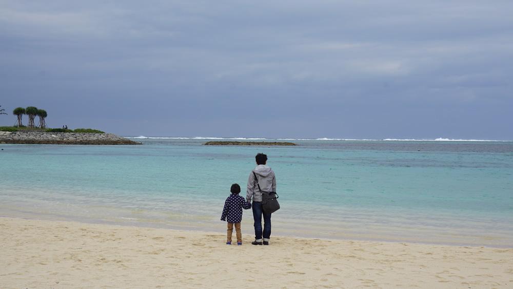 ビーチに臨む息子とパパ